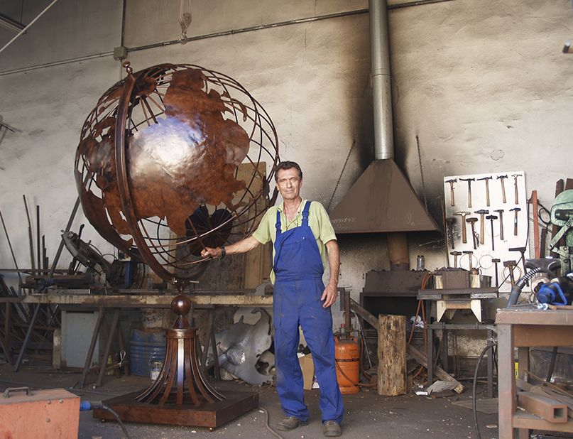 Vicente Gragera con su obra de Bola del Mundo en forja de hierro